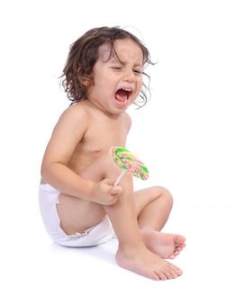 Porträt des weinens des kleinen jungen halten eine süßigkeit lokalisiert auf weißem hintergrund
