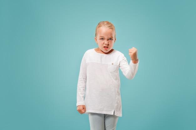 Porträt des wütenden jugendlich mädchens auf einem blauen studio