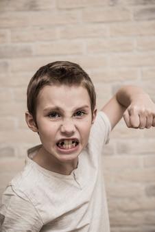 Porträt des wütenden kaukasischen kleinen tyrannjungen mit stilvollem haarschnitt, der wütenden gesichtsausdruck macht und gepumpte faust hält