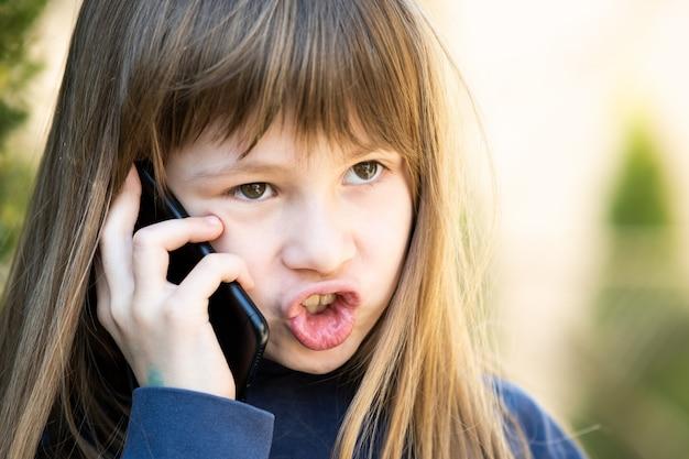 Porträt des wütenden kindermädchens mit den langen haaren, die auf handy sprechen. kleines weibliches kind, das diskussion auf smartphone hat. kommunikationskonzept für kinder.