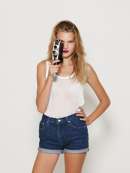 Porträt des wunderschönen weiblichen blonden modells, das in weißer modekleidung posiert und eine retro-kamera in der hand hält