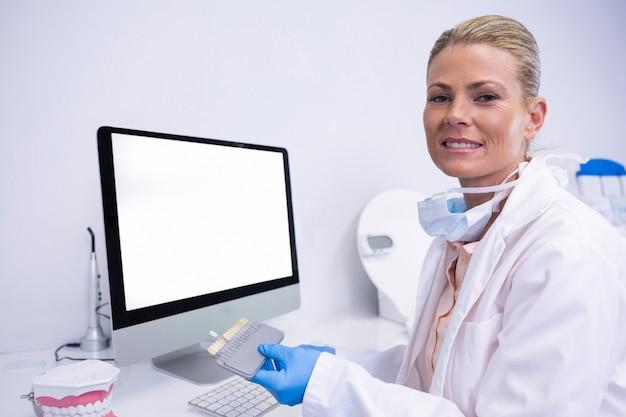 Porträt des zahnarztes, der beim sitzen am computer arbeitet