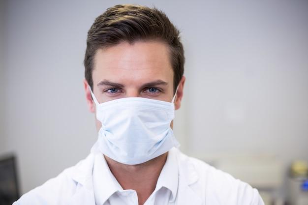 Porträt des zahnarztes, der chirurgische maske trägt