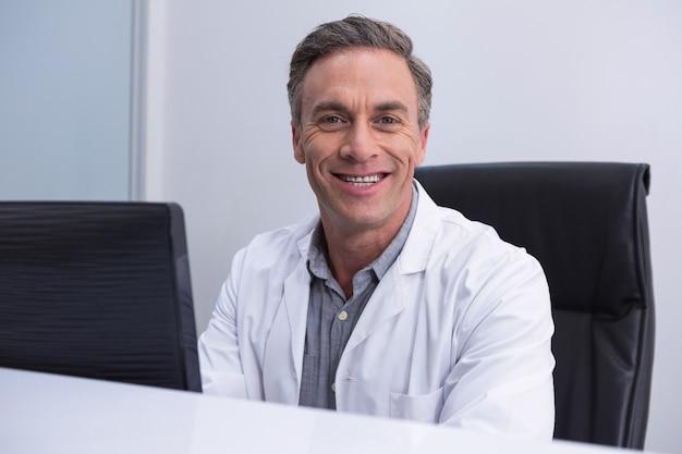 Porträt des zahnarztes, der durch computer am tisch sitzt