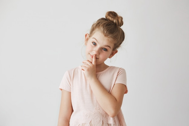 Porträt des zarten kleinen mädchens mit blondem haar in der brötchenfrisur, finger auf den lippen haltend und lächelnd, mit ruhigem gesichtsausdruck.