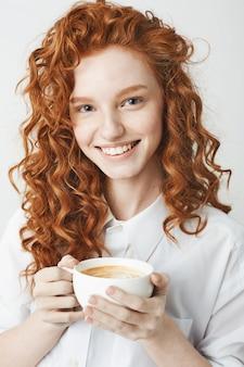 Porträt des zarten rothaarigen mädchens mit den sommersprossen lächelnd, die tasse halten