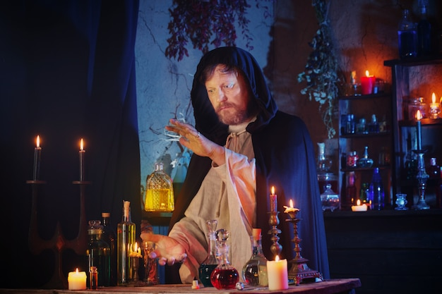 Porträt des zauberers mit brennenden kerzen und zaubertränken