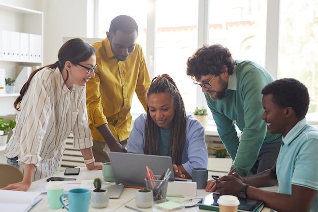Porträt des zeitgenössischen multiethnischen teams, das sich über laptop beugt und während der zusammenarbeit im büro lächelt