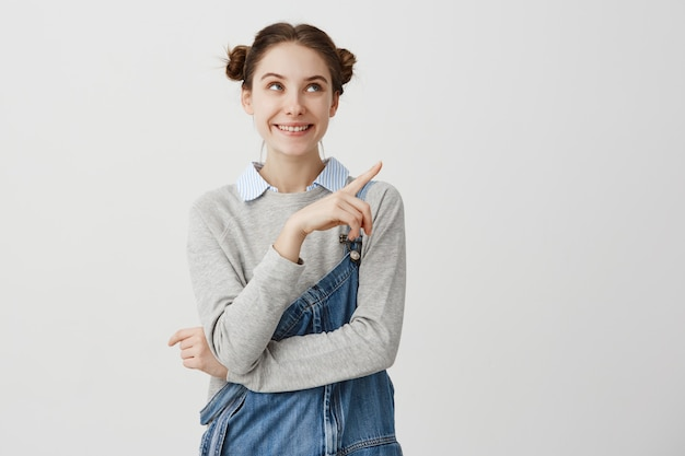 Porträt des ziemlich positiven erwachsenen mädchens mit den doppelten brötchen, die finger weg zeigen. junge architektin mit würde, die ihre arbeit auf weißer wand demonstriert. speicherplatz kopieren