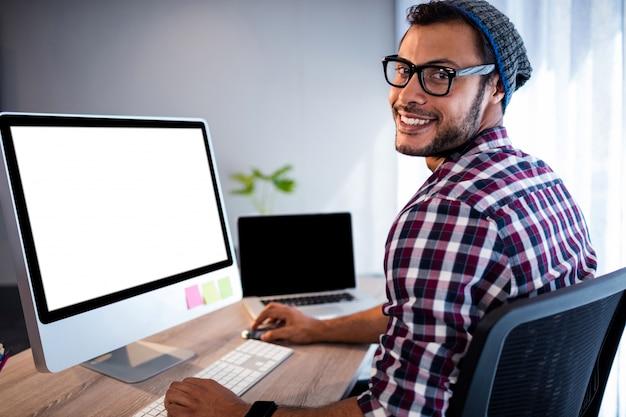 Porträt des zufälligen mannes arbeitend am computertisch