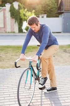 Porträt des zufälligen mannes, der fahrrad draußen reitet