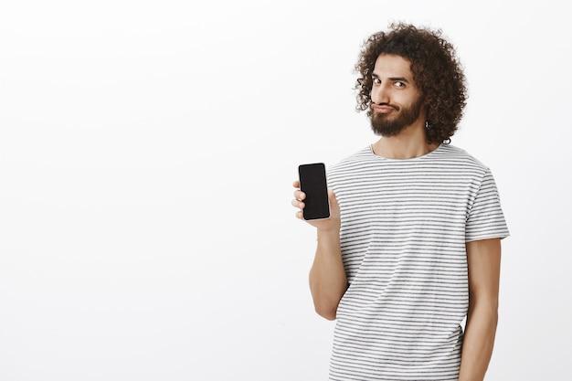 Porträt des zufriedenen verspielten östlichen bärtigen mannes mit afro-haarschnitt, smartphone zeigend