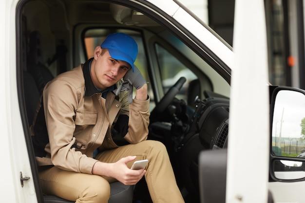 Porträt des zustellers in der uniform, die handy hält und kamera beim sitzen im van betrachtet