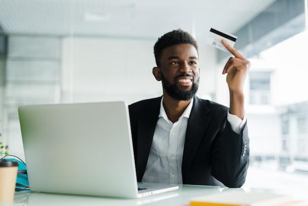 Porträt des zuversichtlichen jungen afrikanischen mannes, der kreditkarte mit laptop hält, der über internet zahlt