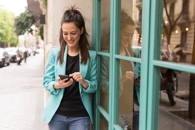 Porträt draußen der jungen glücklichen bloggerfrau mit handy. glasfenster hintergrund. freizeitkleidung tragen. spaß und lebensstil