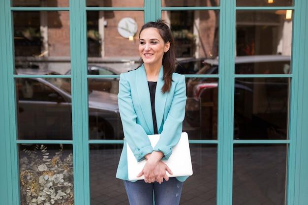 Porträt draußen der jungen glücklichen bloggerfrau mit modernem laptop. glasfenster hintergrund. freizeitkleidung tragen. spaß und lebensstil