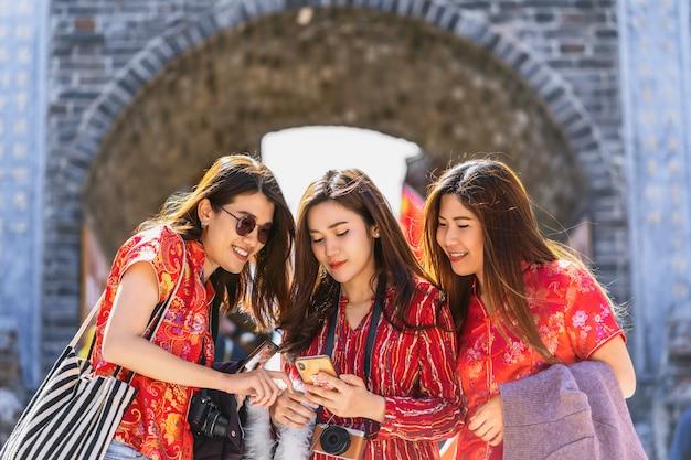 Porträt drei asiatische glückfrauen, die zusammen intelligenten handy für soziales netz verwenden