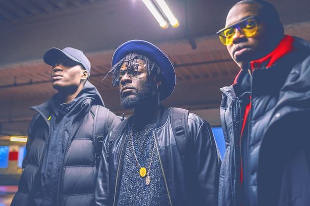 Porträt drei junge schwarze männer, die in einem parkplatz weg schaut aufwerfen