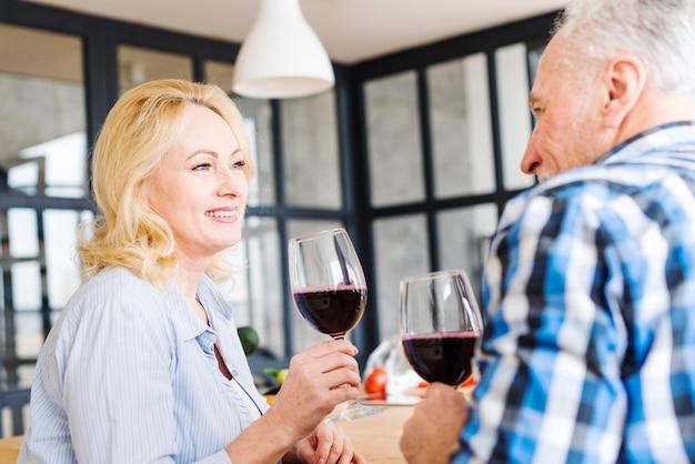Porträt einer älteren blondine, die den wein mit seinem ehemann in der küche trinkt