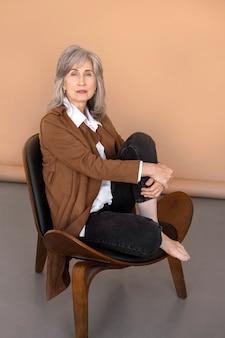 Porträt einer älteren eleganten frau, die auf einem stuhl sitzt