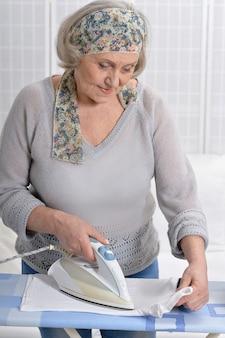 Porträt einer älteren frau beim bügeln