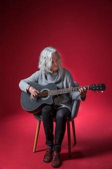 Porträt einer älteren frau, die auf dem stuhl spielt die gitarre gegen roten hintergrund sitzt