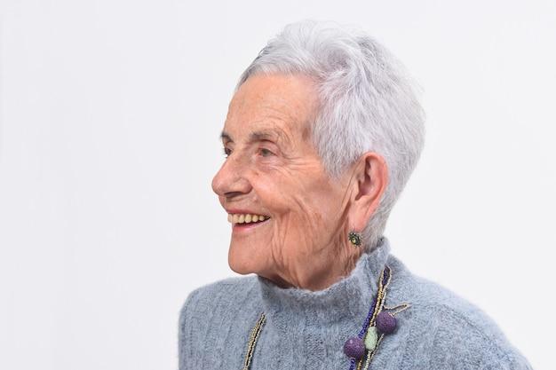 Porträt einer älteren frau, die auf weißem hintergrund lächelt