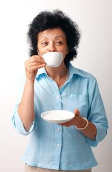 Porträt einer älteren frau, die aus einer tasse trinkt und eine untertasse hält