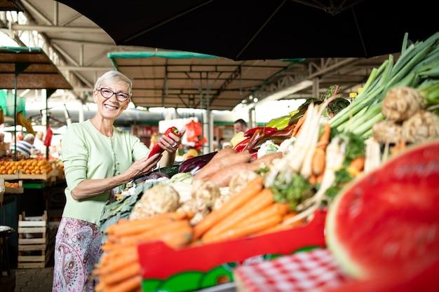 Porträt einer älteren frau, die bio-gemüse am marktplatz hält und kauft.