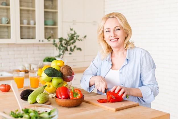 Porträt einer älteren frau, die den roten grünen pfeffer mit messer auf hackendem brett in der küche schneidet