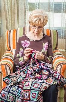 Porträt einer älteren frau, die eine vintage-wolldecke mit bunten flecken strickt