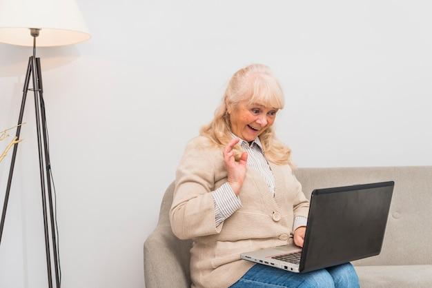 Porträt einer älteren frau, die ihre hand bei der anwendung der digitalen tablette wellenartig bewegt
