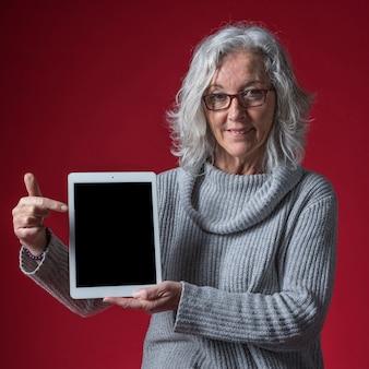 Porträt einer älteren frau, die ihren finger auf digitale tablette gegen farbigen hintergrund zeigt