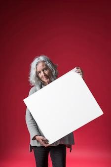Porträt einer älteren frau, die in der hand weißes plakat gegen roten hintergrund hält