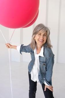 Porträt einer älteren frau, die in einer jeansjacke posiert und rosa luftballons hält