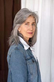 Porträt einer älteren frau, die in einer jeansjacke posiert