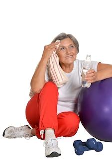 Porträt einer älteren frau, die nach dem training auf einem boden mit wasser sitzt, isoliert auf weiß