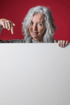 Porträt einer älteren frau, die nach unten ihren finger das weiße leere plakat zeigt