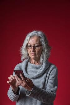 Porträt einer älteren frau, die smartphone gegen roten hintergrund verwendet