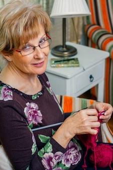 Porträt einer älteren frau, die zu hause einen wollpullover strickt