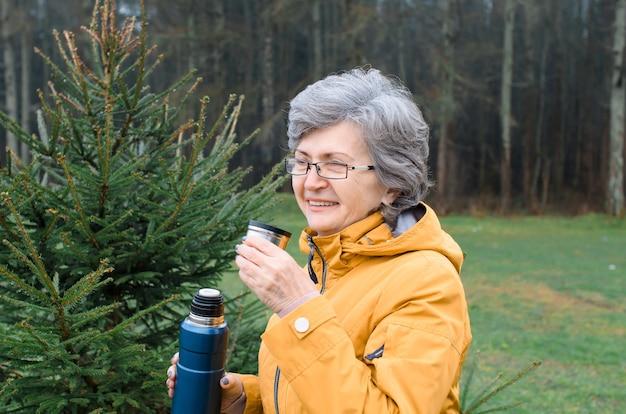 Porträt einer älteren frau draußen im wald. ältere frau lächelt und trinkt heißen tee beim gehen. wanderkonzept, wärmendes getränk bei kaltem wetter.