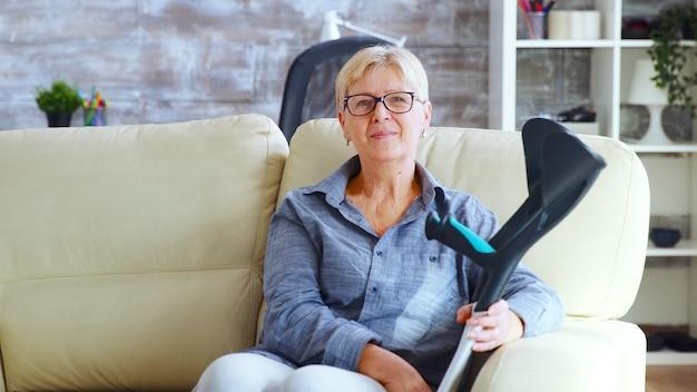 Porträt einer älteren frau im pflegeheim, die auf der couch sitzt und aussieht, als wäre sie verloren