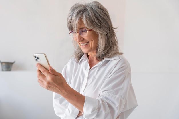 Porträt einer älteren frau mit einem smartphone-gerät
