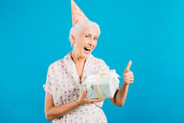 Porträt einer älteren frau mit geburtstagsgeschenk daumen oben auf blauem hintergrund gestikulierend