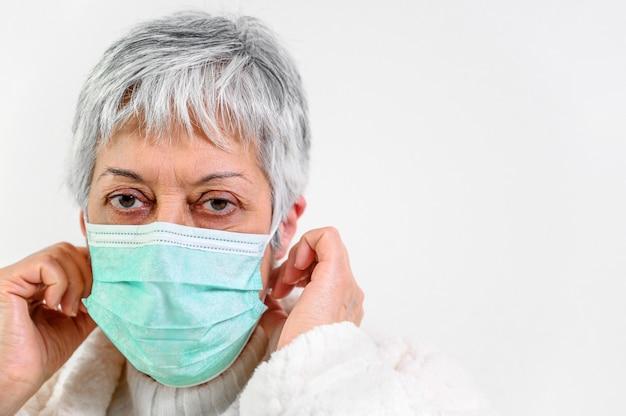 Porträt einer älteren frau mit gesichtsschutzmaske.