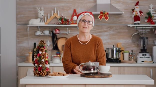 Porträt einer älteren frau mit weihnachtsmütze, die am tisch in der weihnachtlich dekorierten küche steht