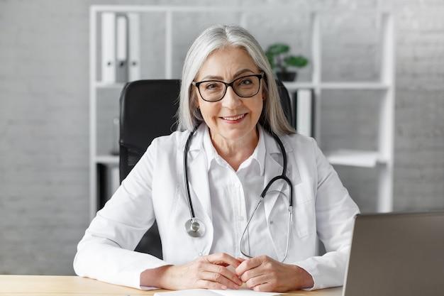Porträt einer älteren grauhaarigen ärztin in ihrem büro mit laptop für video-chat mit einem patienten. online-konsultation mit dem arzt für diagnosen und behandlungsempfehlungen. telemedizin-konzept.