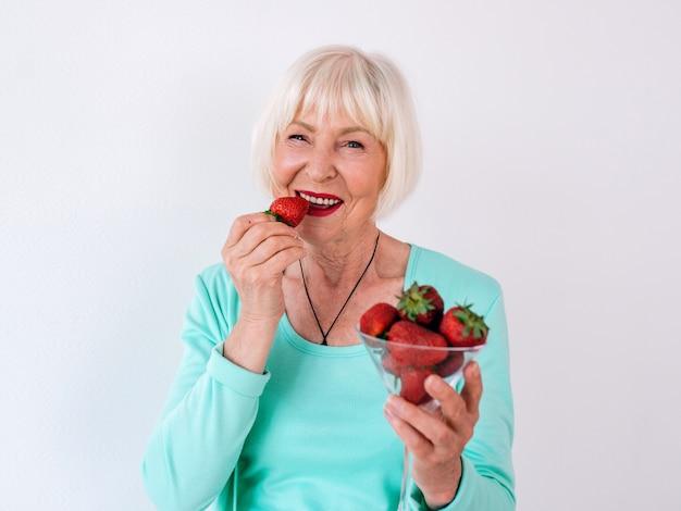 Porträt einer älteren, stilvollen, fröhlichen frau in türkisfarbener kleidung, die erdbeeren isst