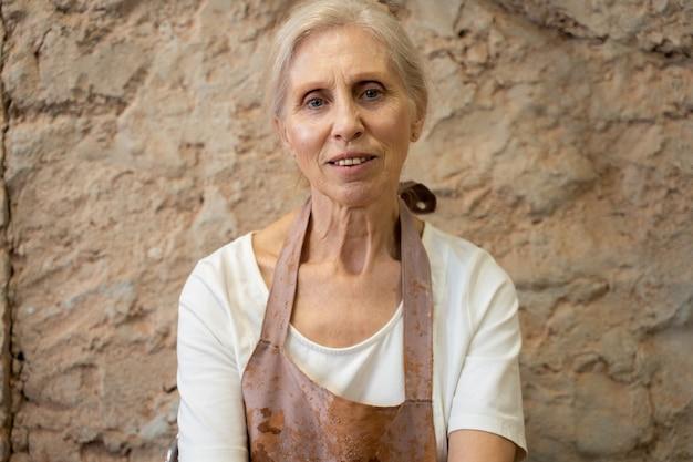 Porträt einer älteren töpferin, die in einer töpferwerkstatt sitzt und in die kamera schaut