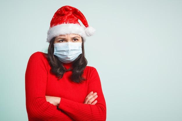 Porträt einer ängstlichen frau in einer roten weihnachtsmütze und einer schützenden medizinischen maske.